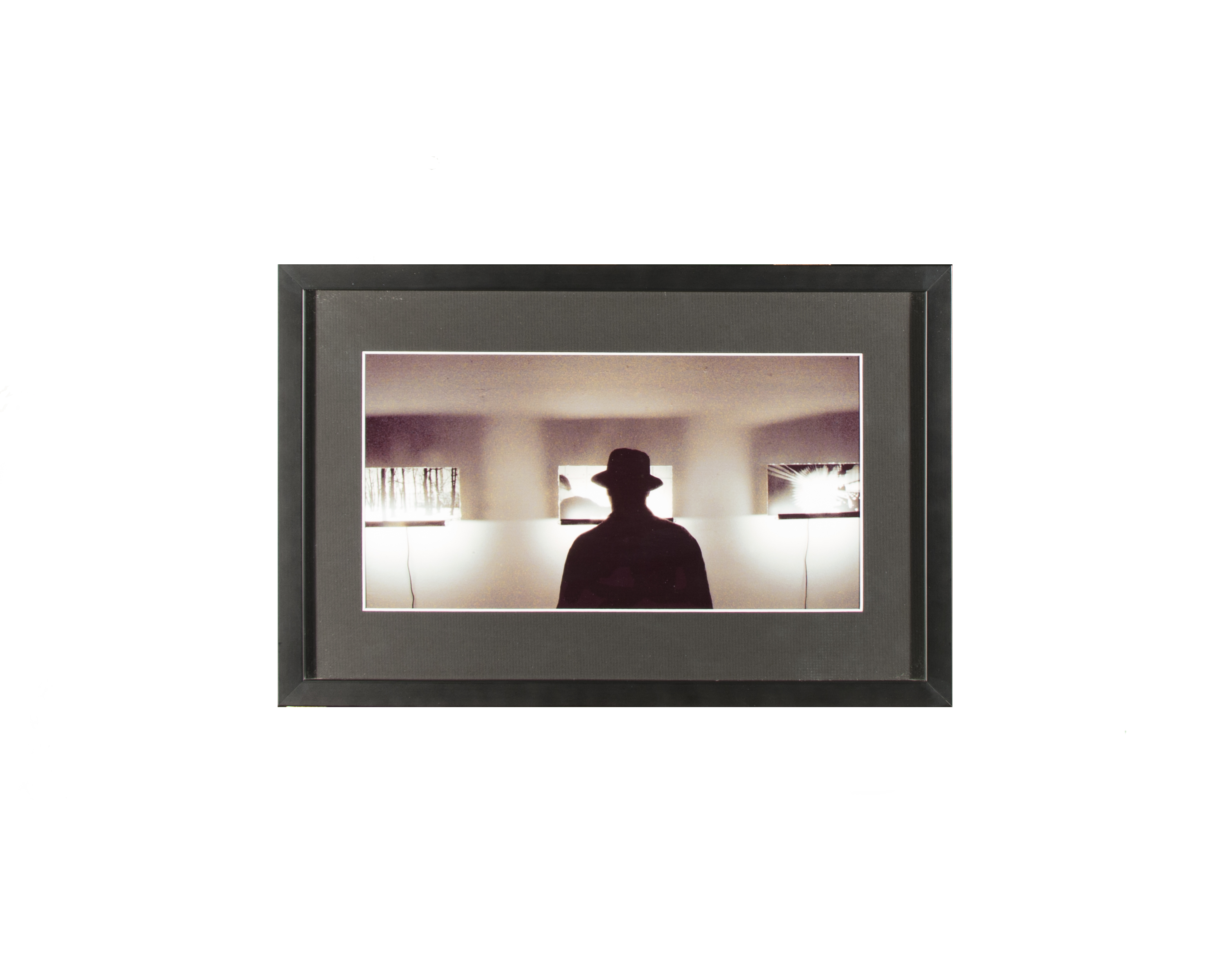 silhouette of a man in a hat in front of three windows