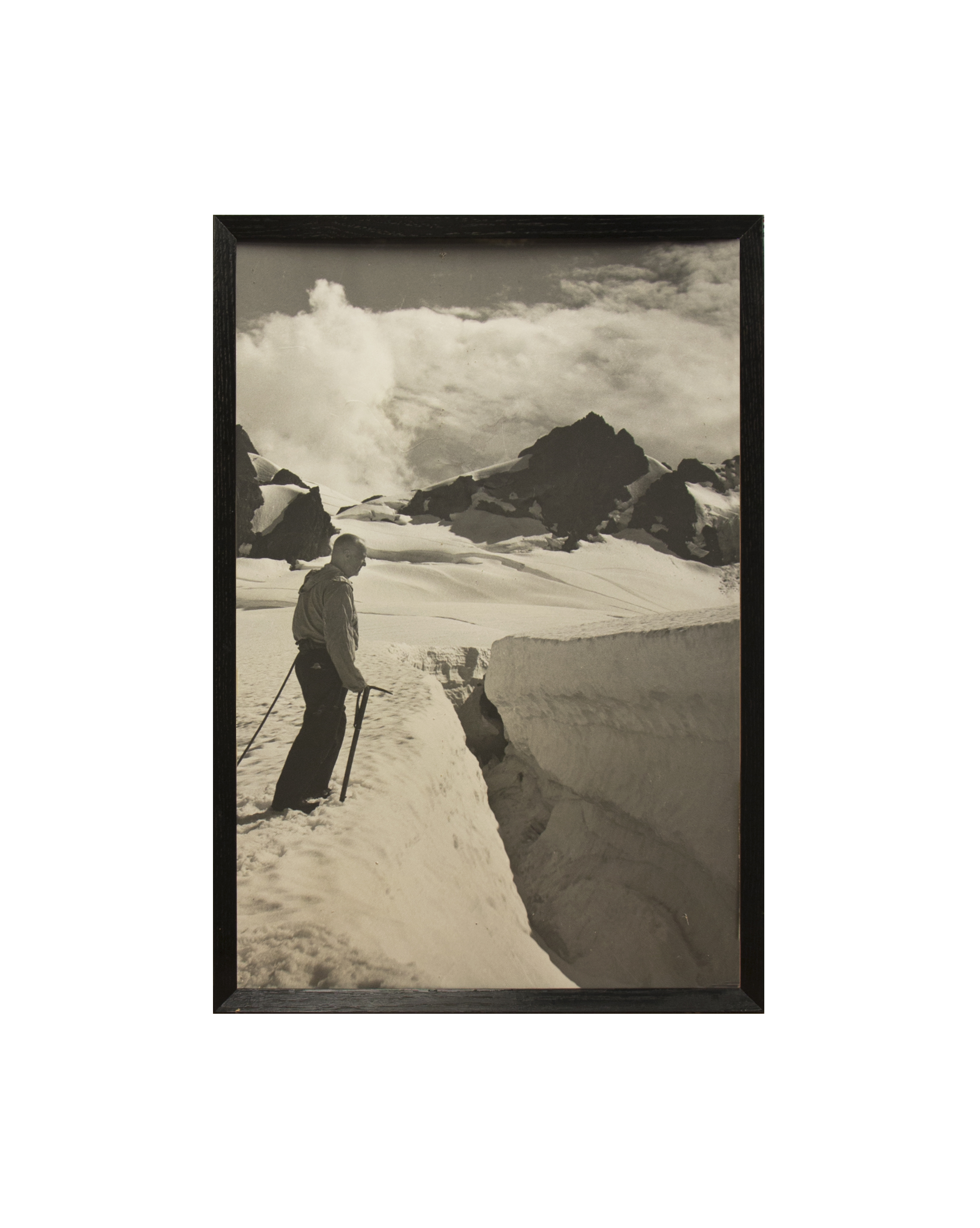 black and while photo of a man on a glacier with Olympic peaks in the distance