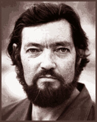 Julio Cortazar, a dark haired, bearded man looks directly at the camera