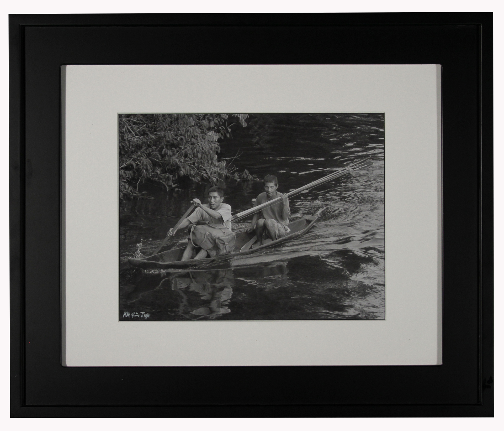 photo of two native men paddling a flat bottomed boat along a  calm river