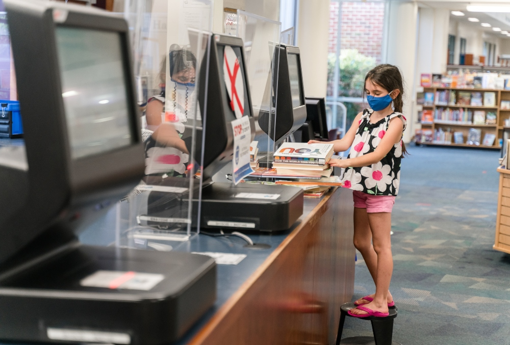 Girl checks out library books.