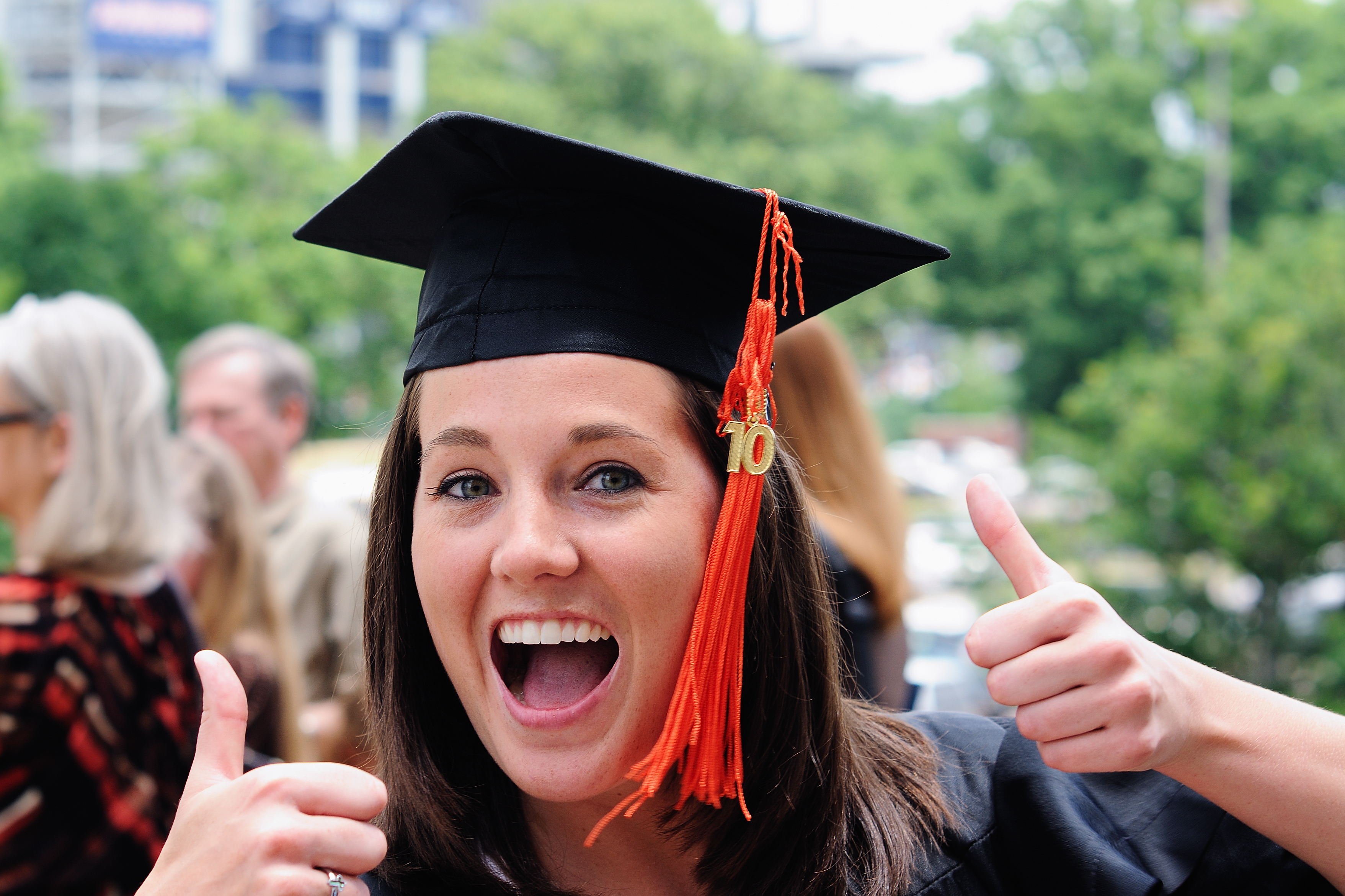 A picture of a lady in a cap in gown giving the thumbs-up sign