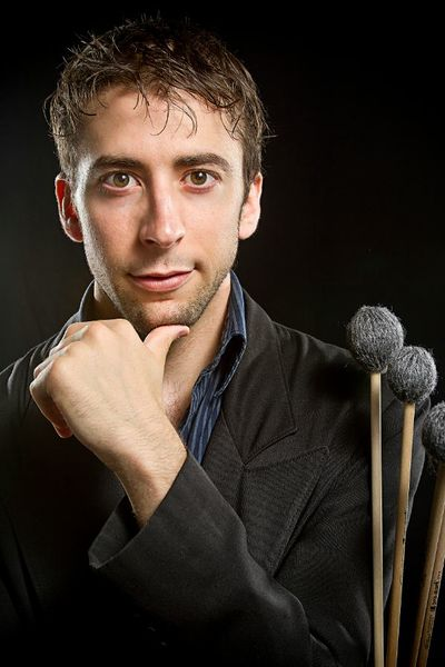 Casey Cangelosi  headshot holding percussion mallets