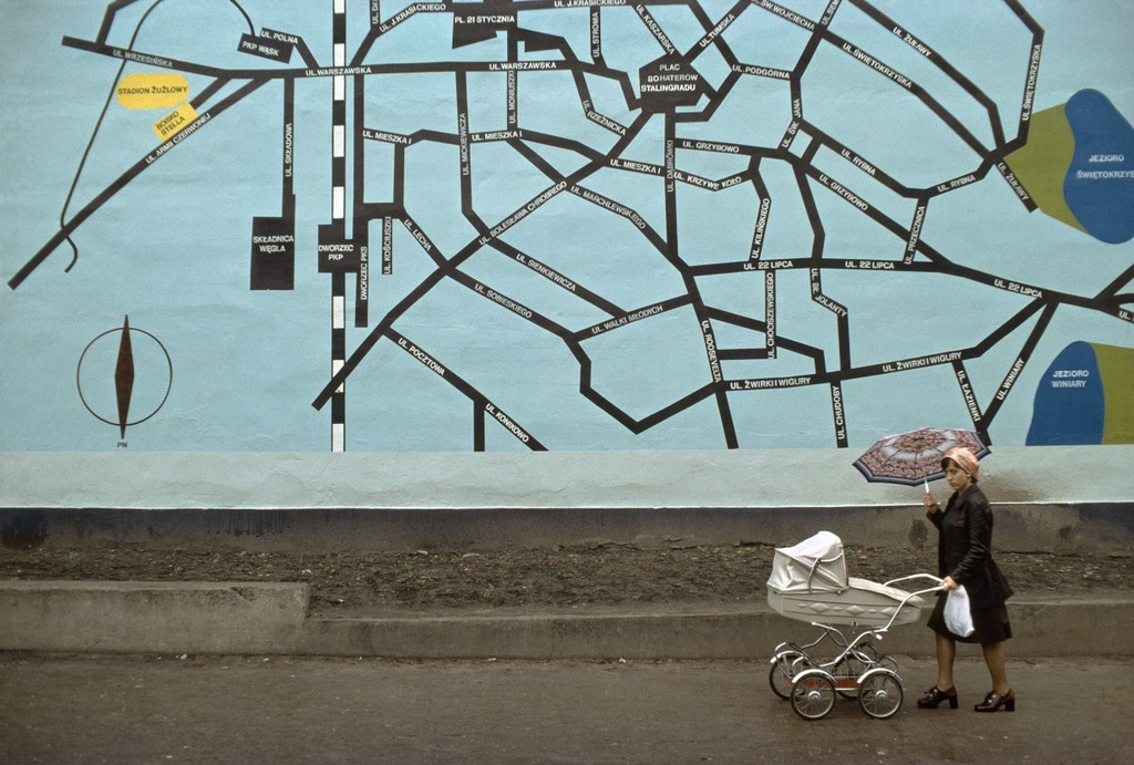 A woman is pictured walking while holding an umbrella and pushing a white baby carriage through Poland.