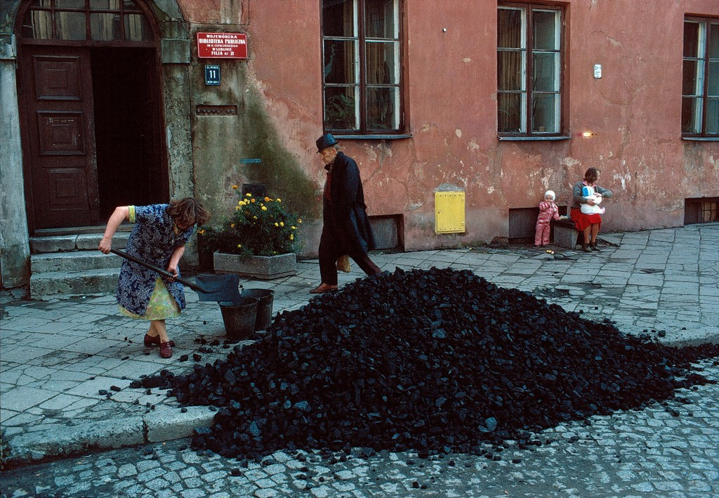 An image from the Town of Chelmno in Poland. A lady is pictured with a shovel collecting coal off a sidewalk in front of a building. A man is walking the sidewalk and a mother with two childen sit and watch at a distance.