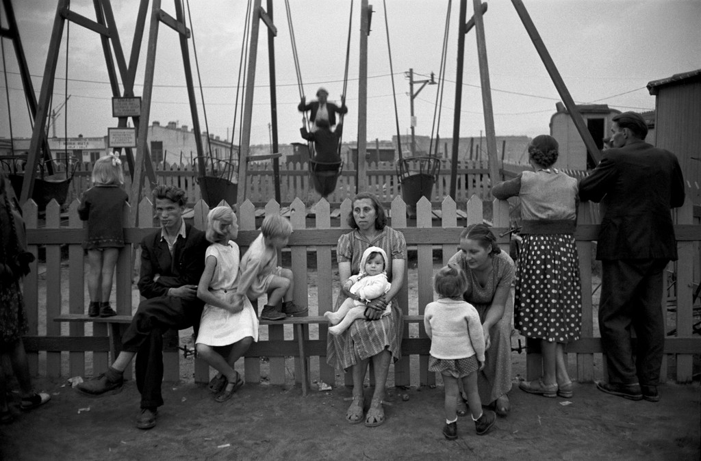 Black & white photo of people adults and kids along a fence in Poland with a playground in the background.