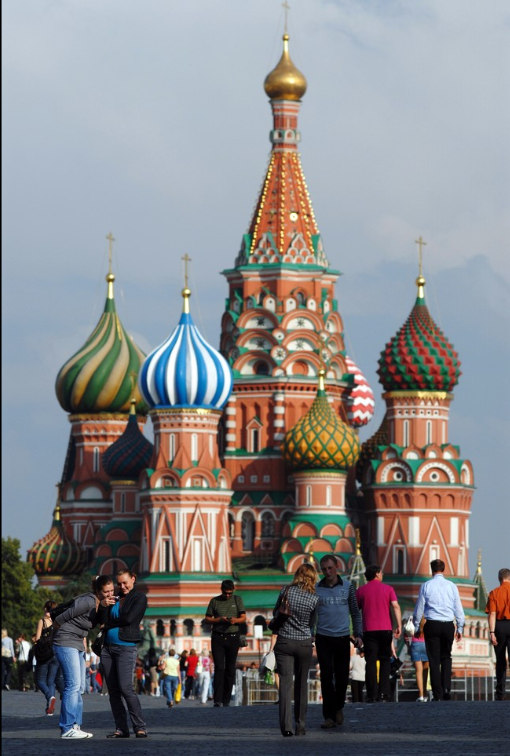 Tourists walk in front of St Basil's Orthodox Cathedral in Red Square