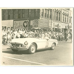 Photograph of a parade with a League of Women Voters car.
