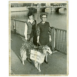 Image of two women with a dog. The dog is wearing a sign that reads