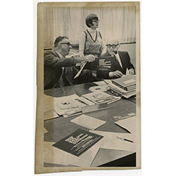 Image of two men sitting at a table looking at a pamphlet with a women standing behind them.