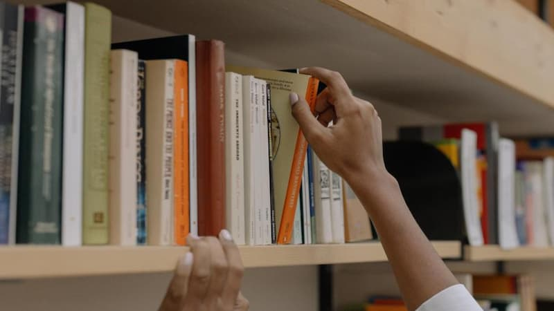 a hand is removing a book from a shelf of books