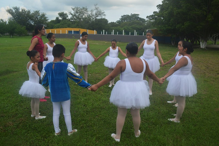 visually disabled girls in tutus holding hands standing in a circle doing a dance