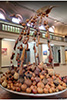Exhibit of many gourds piled on top of each other with one higher up ladle spilling gourds into the pile