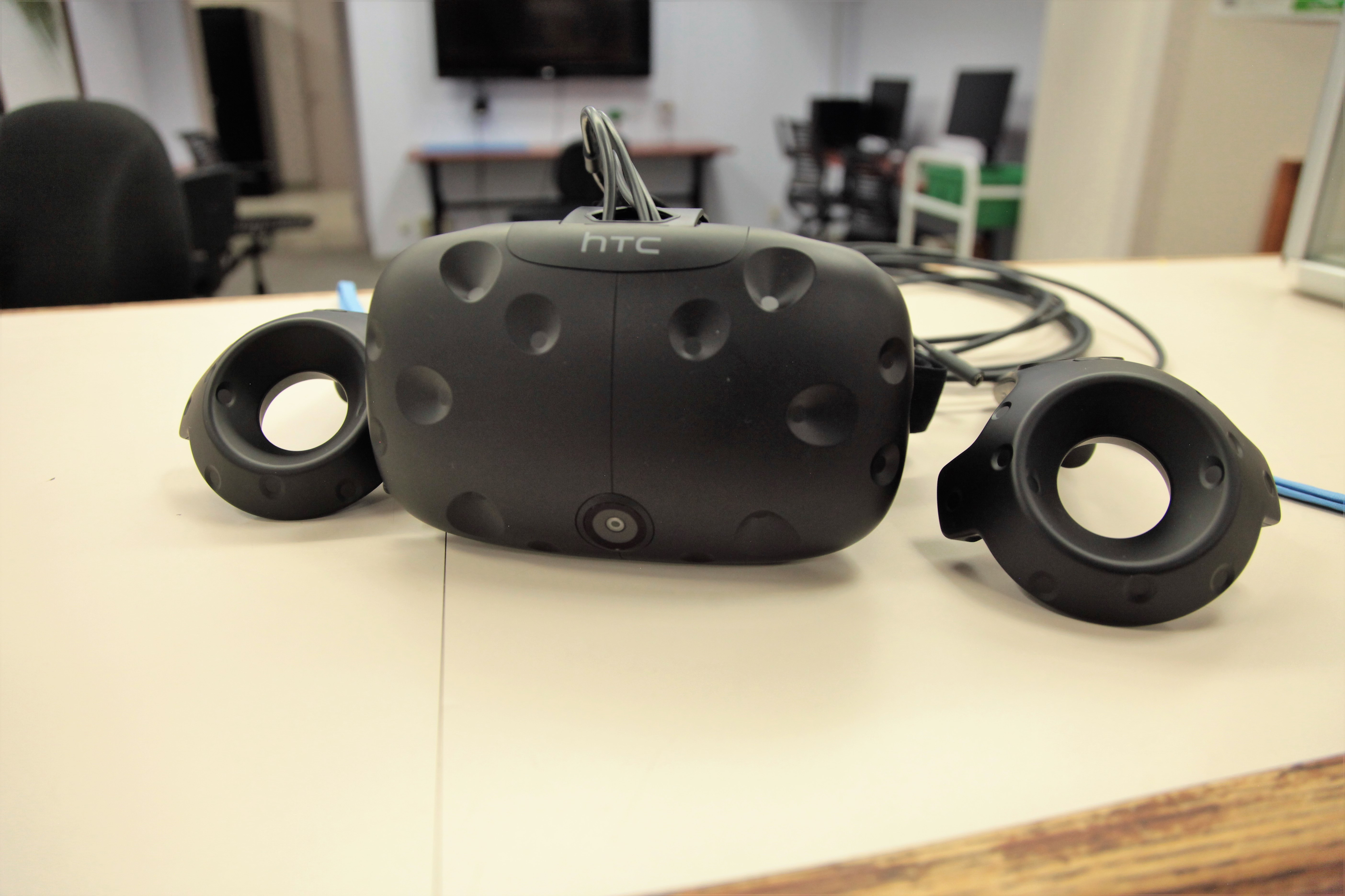An HTC Vive headset and two controllers sitting on a counter