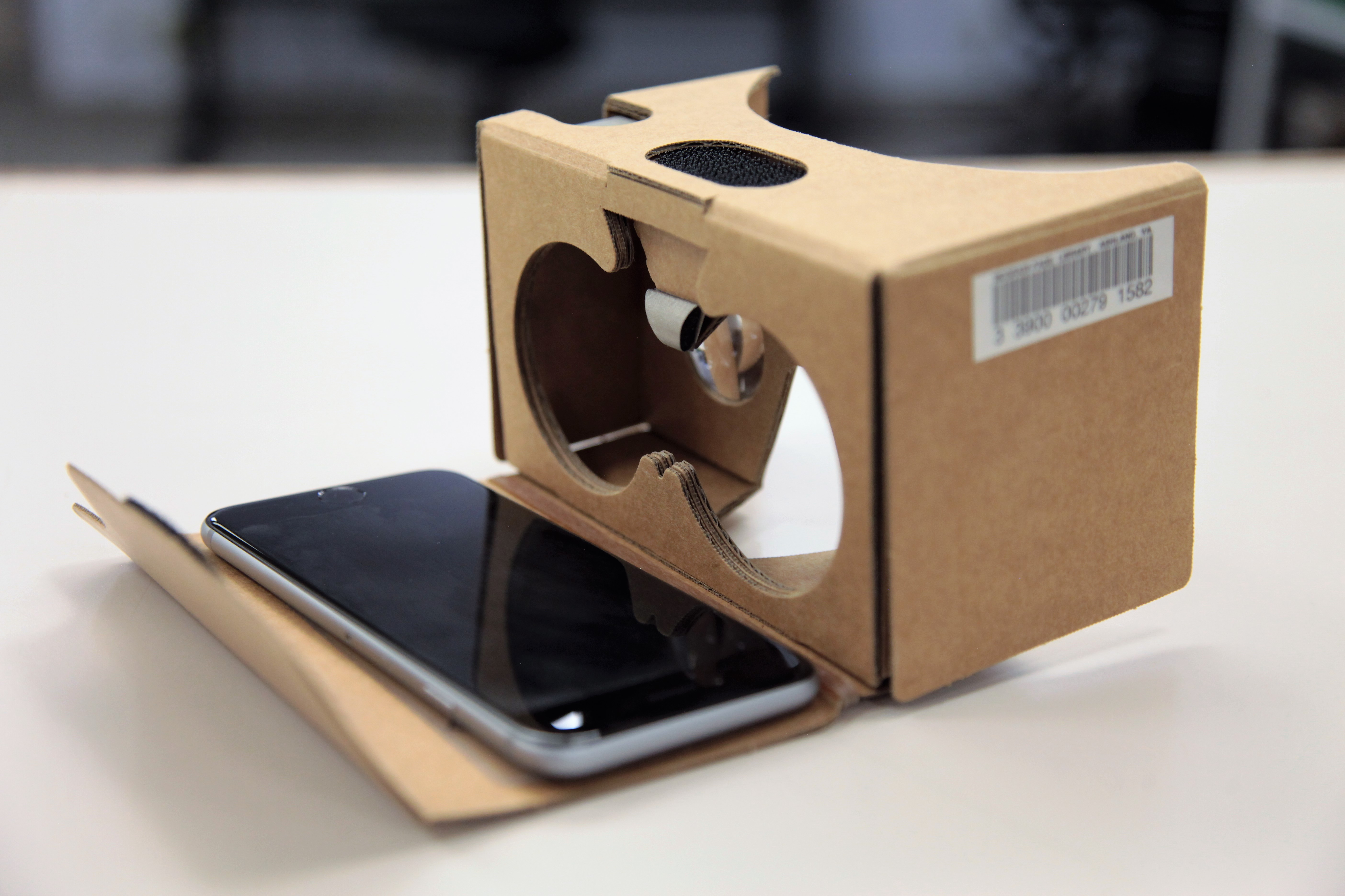 A Google Cardboard Virtual Reality headset with a smart phone sitting on its front flap