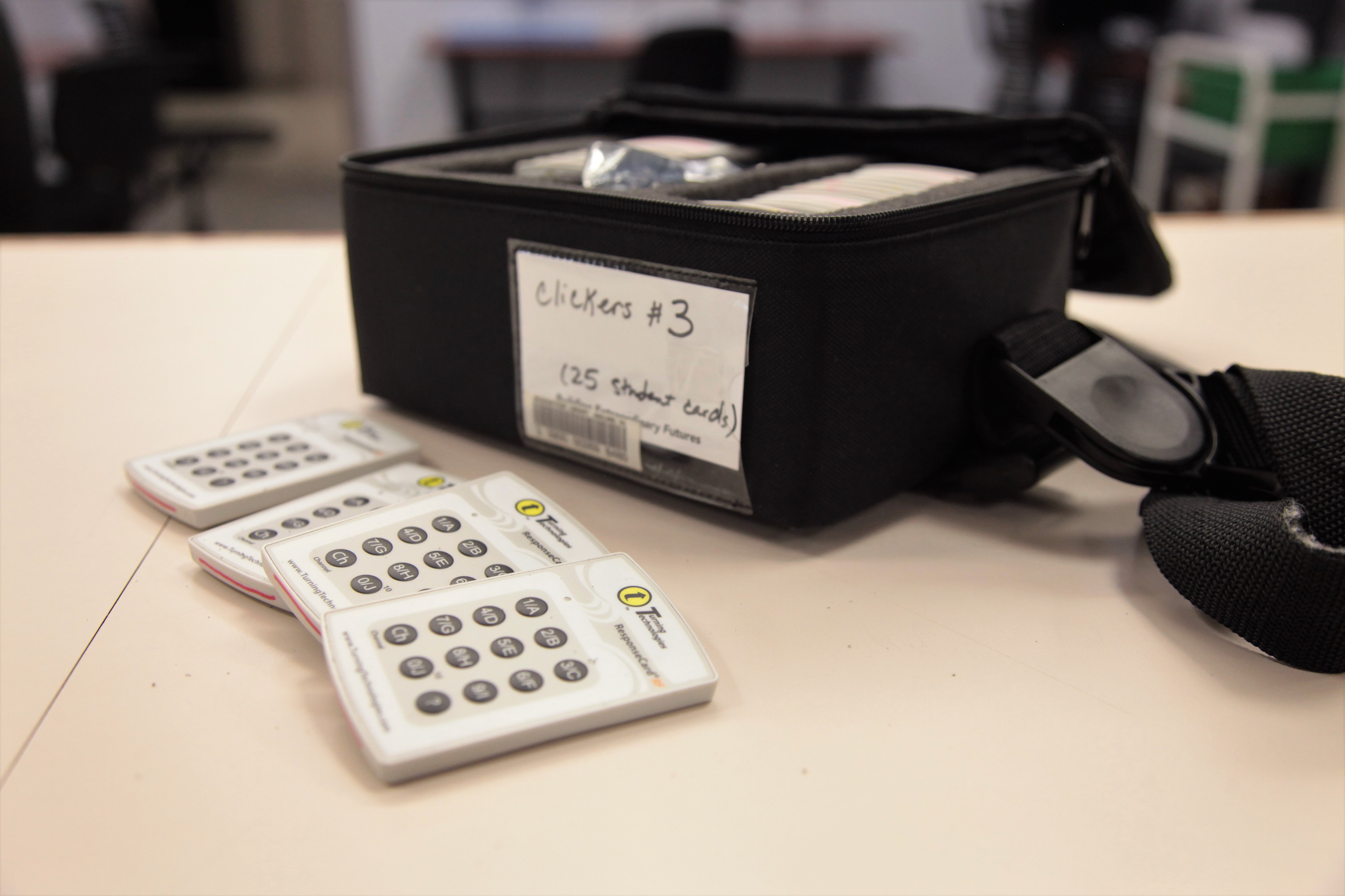A bag of presentation clickers with four clickers spread in front
