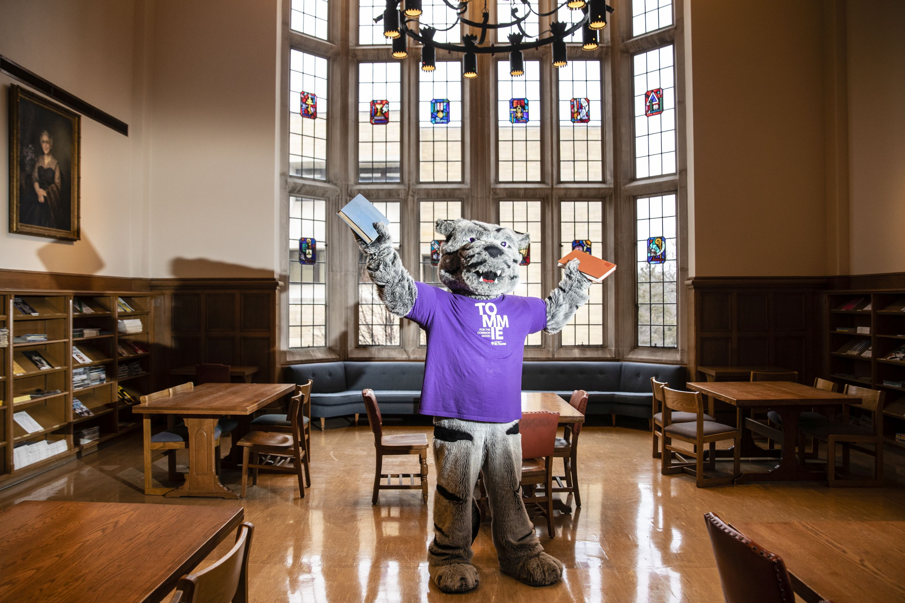 photo of Tommie mascot in the library's great hall holding books