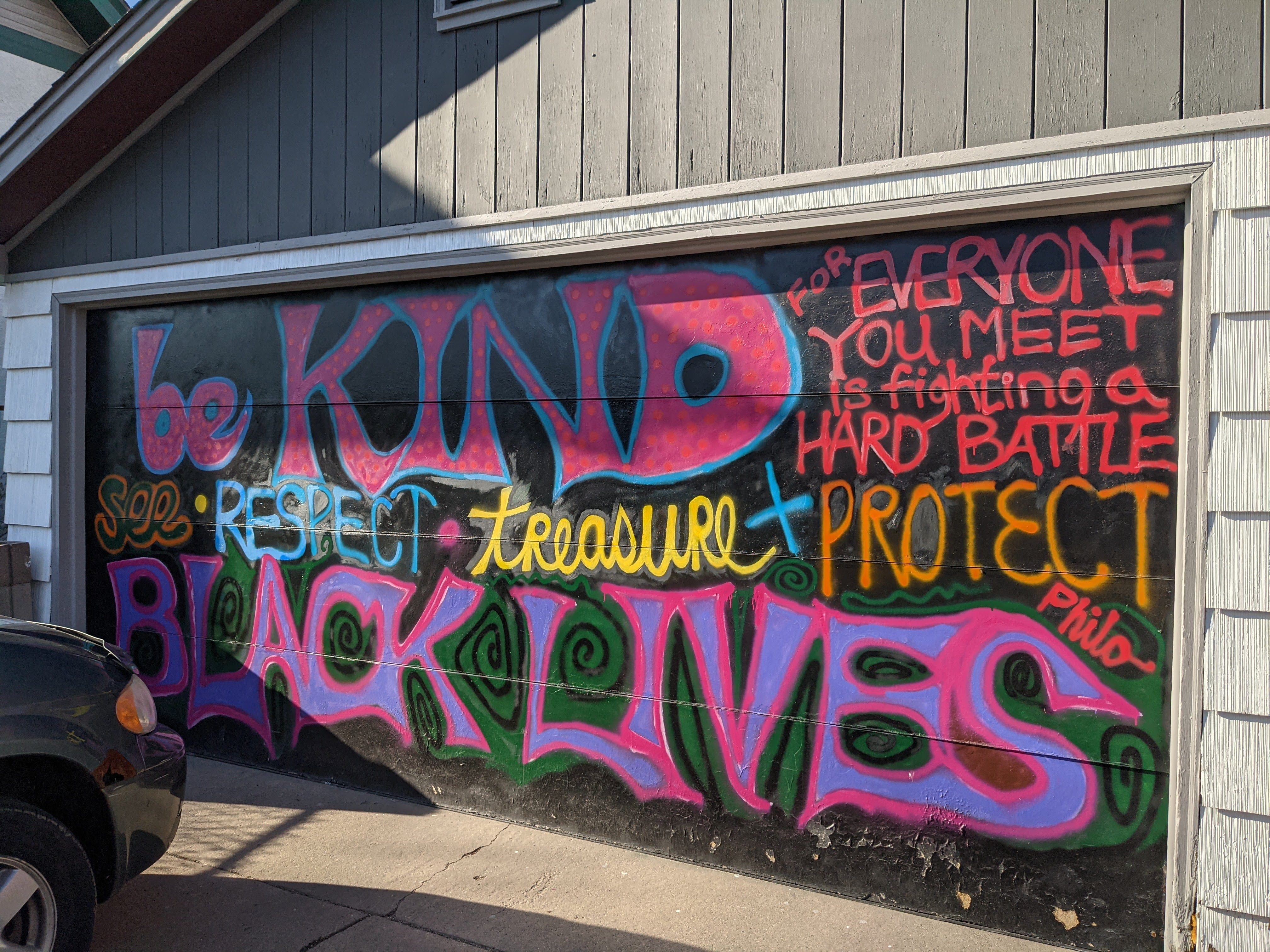 """Private residence parking garage door with stylized text reading """"Be kind for everyone you meet is fighting a hard battle. See, respect, treasure and protect Black lives."""" Philo is written on the slant of the 's' in 'lives'."""