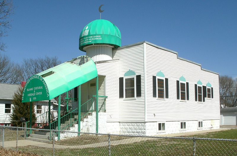 "Front and right side view of a white, one-storey building in the suburbs with a green awning covering the stairs and green accents around the windows. On the front of the awning is printed the words ""The Mother Mosque of America: Islamic Cultural & Heritage Center"". Above the stairs on the front of the building is a small dome, also green, with writing on it, which is not legible."