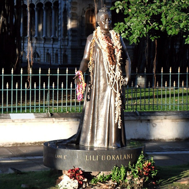 "A bronze statue of a woman draped in flower leis with the text ""Lili'uokalani"" engraved at the base of the statue."