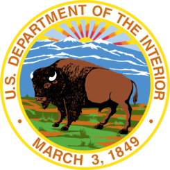 A circular medalion depicting the Department of the Interior Logo surrounded by the agency name. The logo is a bison against a mountainous landscape.