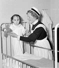 a black and white photo of a nurse and a baby in a crib