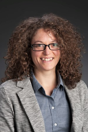 Photograph of Becca Neel: white female, glasses, shoulder-length, brown curly hair, gray blazer