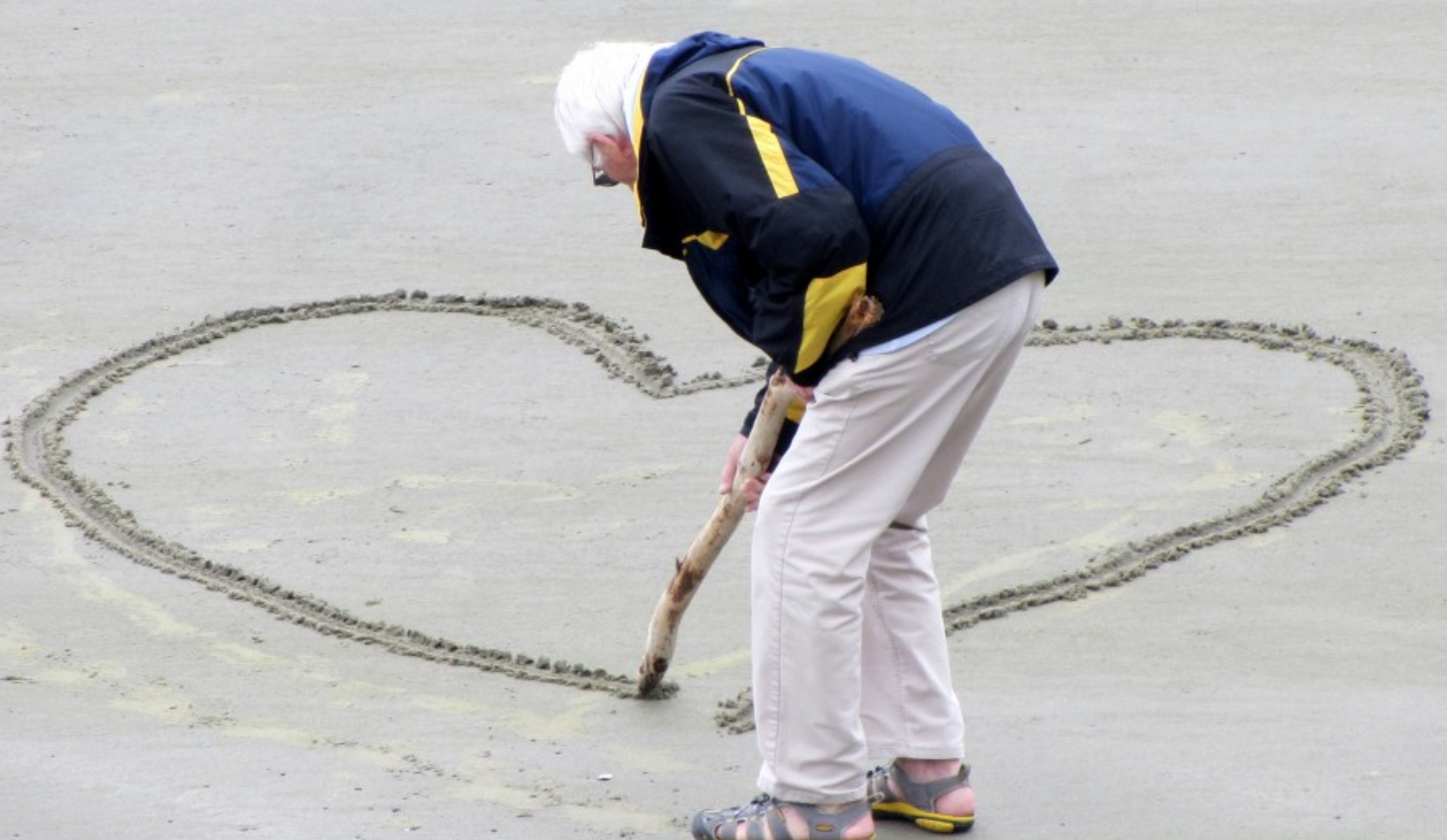 White-haired man on a beach drawing a heart in the sand