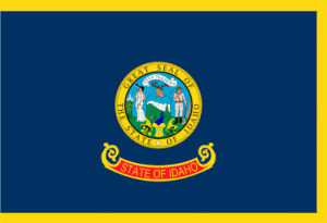 "Idaho state flag, has a blue background and edged in gold, the center seal depicts a miner and a woman, and a red banner has ""State of Idaho"" written in gold."