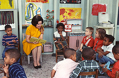 Color image of Ladybird Johnson in a yellow dress reading to a group of schoolchildren.