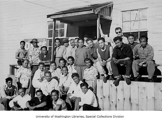 A large group of men, mostly Filipino, standing in front of a white building.