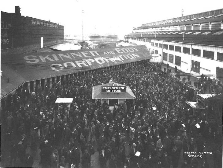 Overhead shot of a large group of men in front of the employment office and building with Skinner and Eddy Corporation in large letters on the roof.