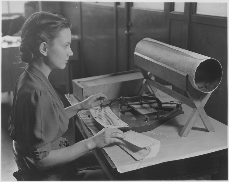 Woman using a card puncher for tabulating census data.