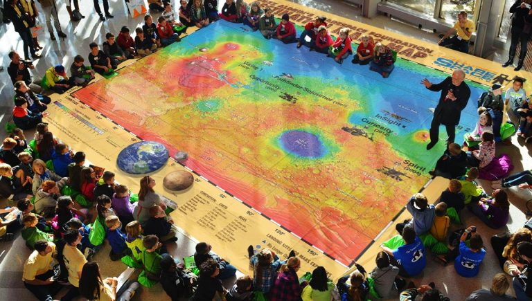 Young students and educators sitting around a large rectangular map.
