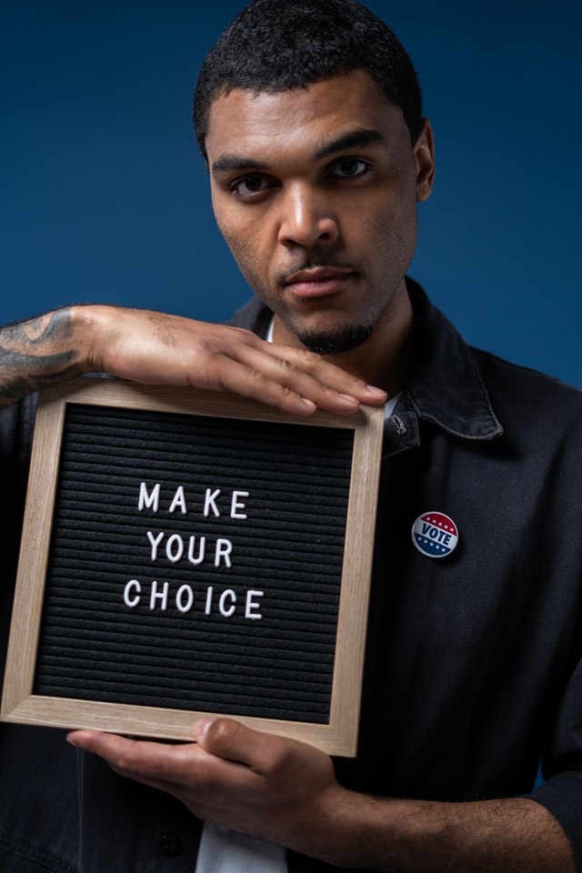 """Man with black hair, brown skin holding a sign that says, """"MAKE YOUR CHOICE."""""""
