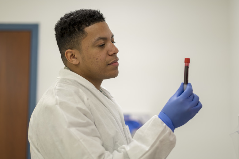 Medical laboratory technologist looks at a vial of blood