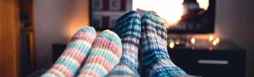 male and female feet in heavy socks in front of TV screen