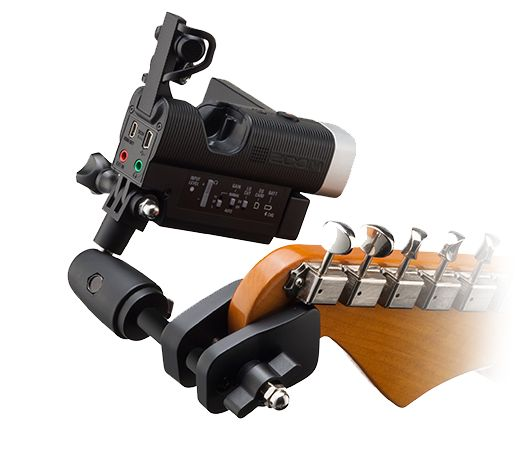 Photo of a Zoom recorder mounted to a guitar using the plastic mount available for checkout.