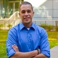 Photo of William D. Lopez, Ph.D--a smiling man with light brown skin, short cropped dark hair, wearing a medium blue button-down shirt; his arms are crossed in front.