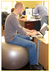 man sitting on stability ball working on laptop