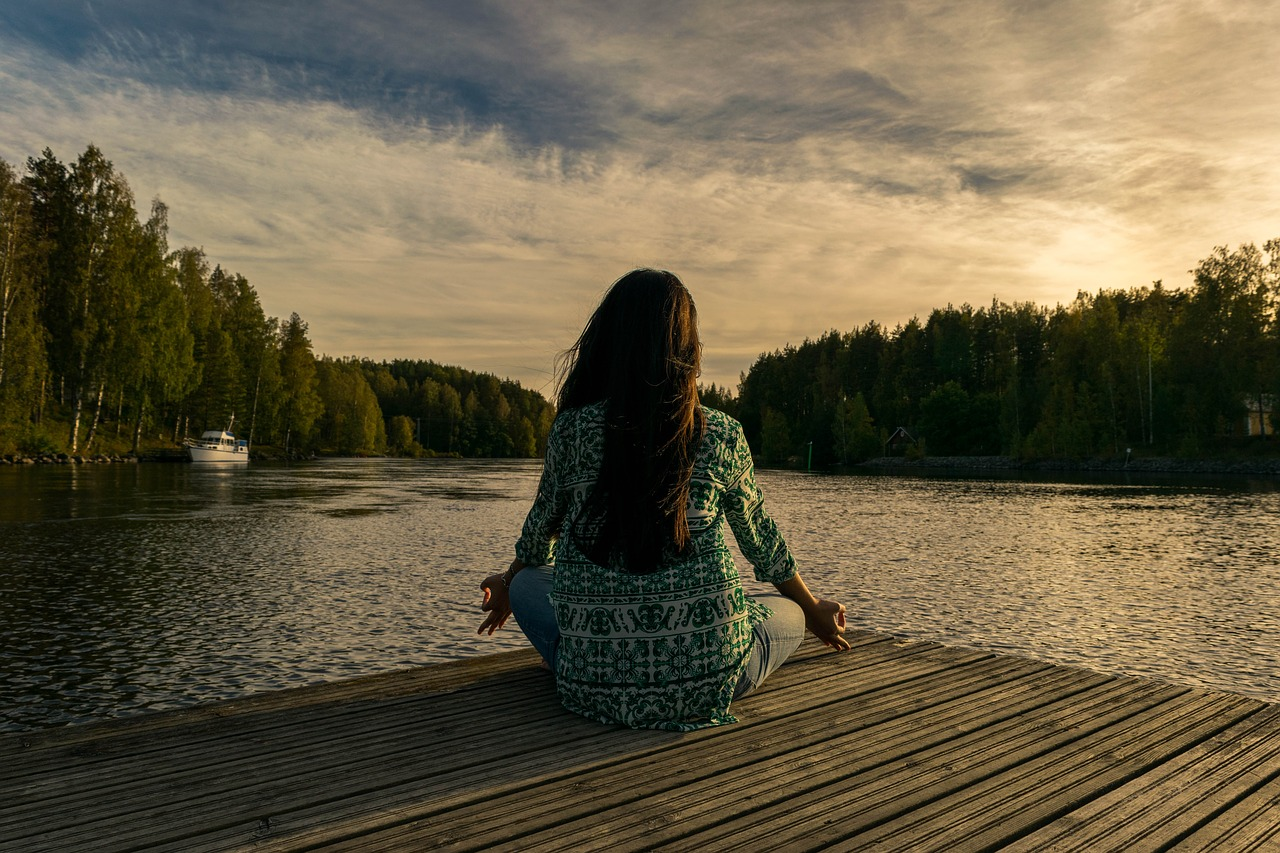 photo of a woman doing yoga on a dock by a lake