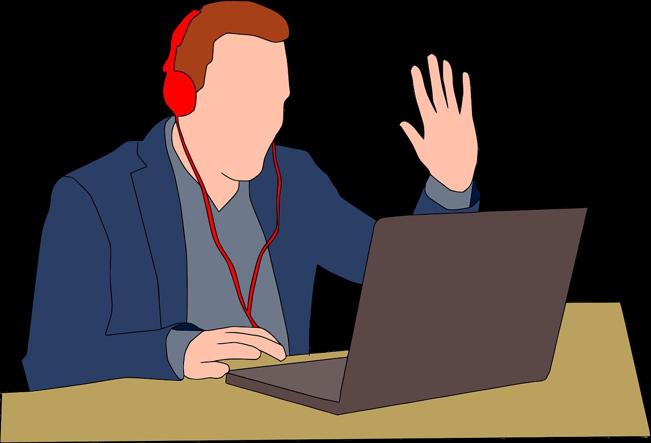 man wearing headphones sitting at laptop raising hand