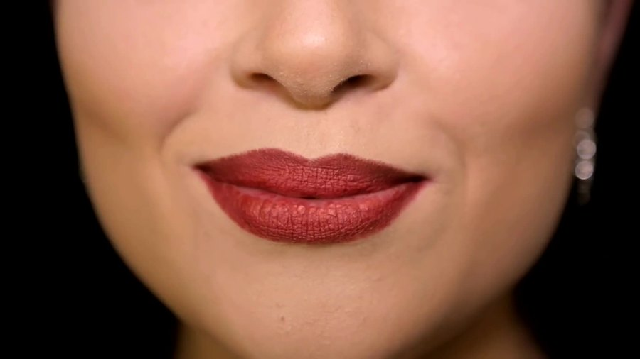 A closeup of a person's lips that have red lipstick