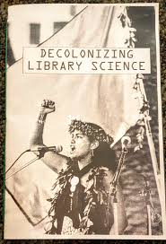 zine cover: Delcolonizing Library Science. Indigenous person at mic, arm raised, hand fisted.