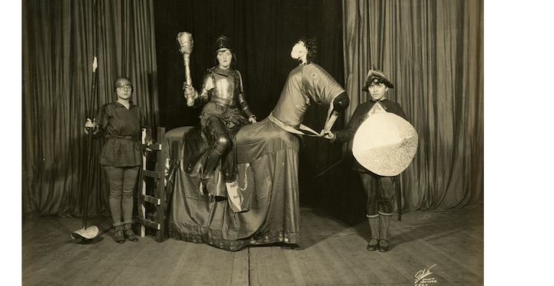 early 20th century photograph of a theater performance: person on a horse, person holding the horse, and person holding a spear.