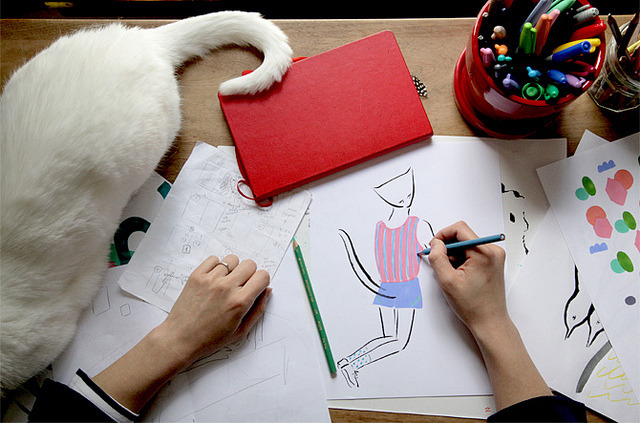 photo of person drawing with a white cat next to them.