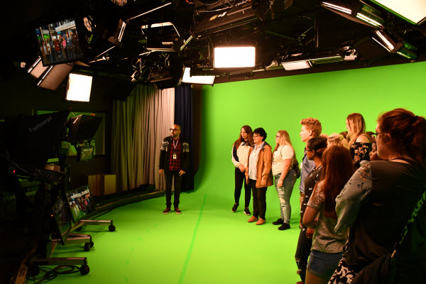 students gathered around a green screen with floating cameras above their heads