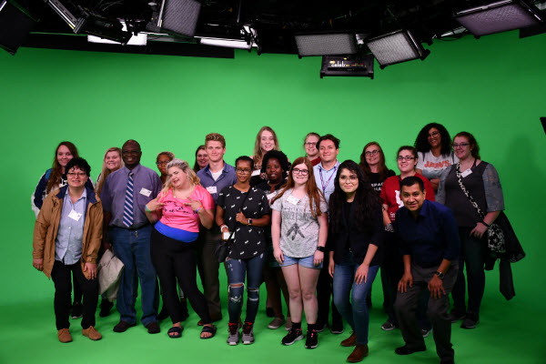 students standing in front a green screen