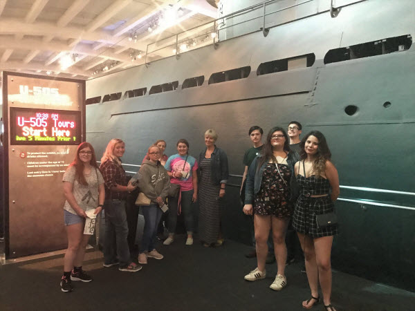 students photographed in front of a submarine