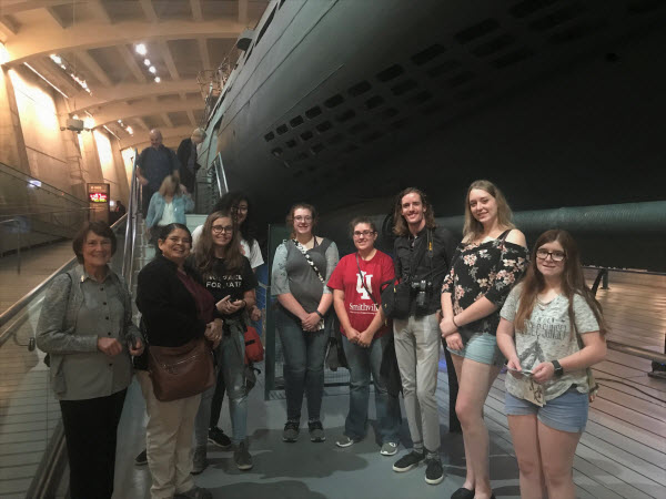 students standing in front of a german submarine